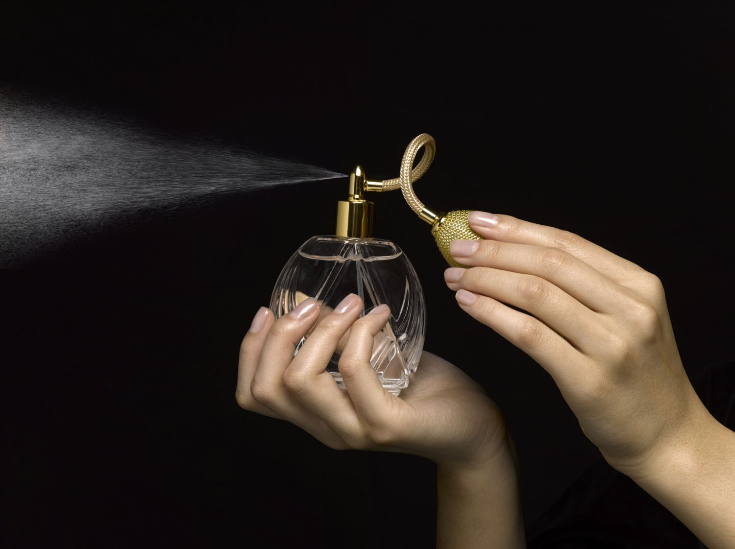 Woman spraying perfume with perfume atomizer, close-up of hands